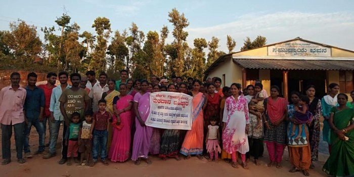 Residents in Chegu village of Mudigere taluk hold a banner declaring their decision to boycott the Lok Sabha elections.
