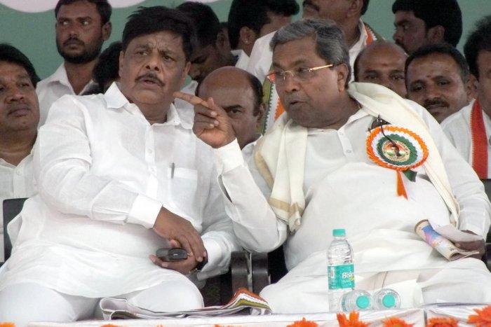 Former minister Dr H C Mahadevappa and former chief minister Siddaramaiah share a word during the Congress Parivarthana rally, in Chamarajanagar, on Friday.