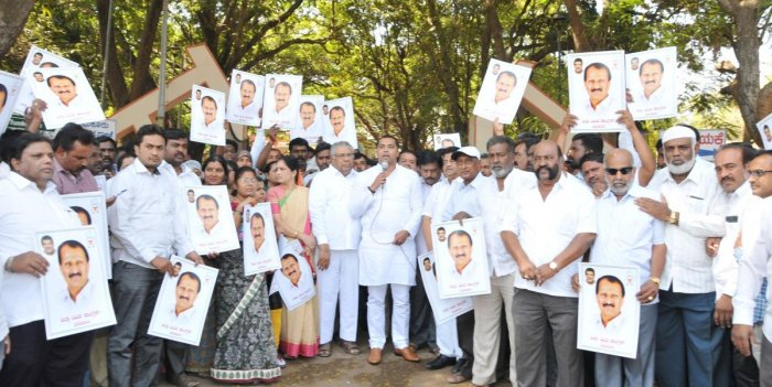 The office-bearers of Tumakuru District Congress Committee and the party workers stage a protest holding pictures of MP S P Muddahanumegowda in Tumakuru on Saturday. DH PHOTO