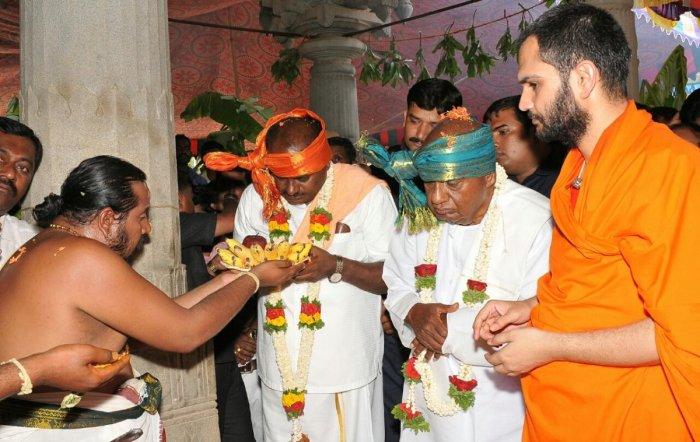 JD(S) supremo H D Deve Gowda and Chief Minister H D Kumaraswamy at Pattanayakanahalli Mutt in Sira taluk, Tumakuru district, on Monday. Nanjavadhootha Swami looks on. DH PHOTO