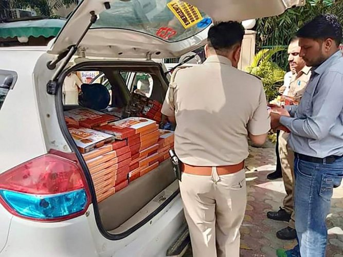 Police seize saffron coloured food packets from 'Namo Foods' which were being distributed outside a polling booth during the first phase of Lok Sabha polls in Gautam Buddh Nagar on Thursday. PTI photo