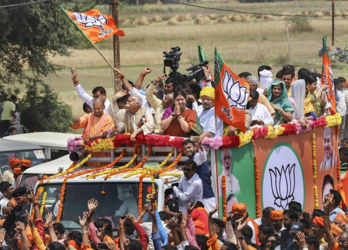 Union minister and BJP candidate Smriti Irani, accompanied by Uttar Pradesh Chief Minister Yogi Adityanath and other leaders, waves at the supporters during a roadshow before filing her nomination papers for Amethi Lok Sabha seat, in Amethi on April 11, 2
