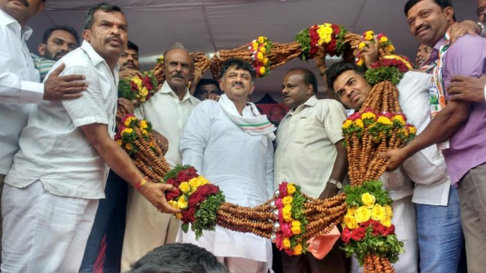 Supporters faciliate Water Resources Minister D K Shivakumar and Chief Minister H D Kumararaswamy with a garland of almonds during an election meeting in Kunigal, Tumakuru district on Friday. DH Photo