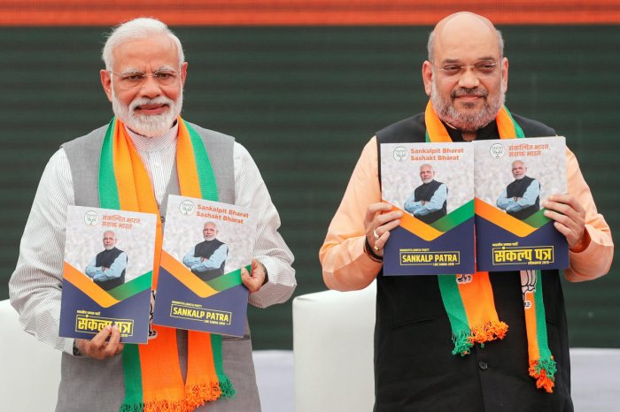 Prime Minister Narendra Modi and BJP chief Amit Shah, display copies of their party's election manifesto for the general election in New Delhi. REUTERS