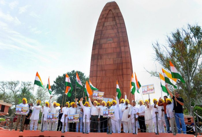 Activists of the All India Anti Terrorist Front (AIATF) hold Indian national flags as they shout patriotic slogans while paying tribute to the martyrs ahead of 100th anniversary of the JallianwalaBagh massacre, at its memorial in Amritsar on Thursday. PTI Photo