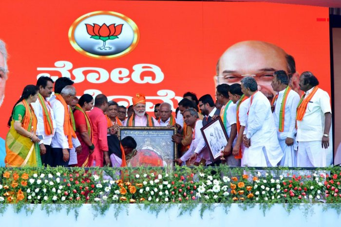 Prime Minister Narendra Modi is presented with a portrait of Anjaneya of Anjanadri, during the election rally in Gangavathi, Koppal district on Friday. DH Photo