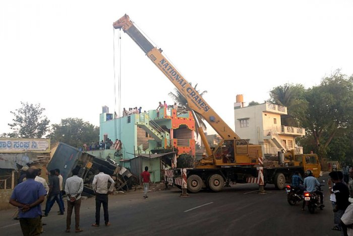 JCB lifting the Sand loaded tripper which kills two persons were their sleep after the truck abandoned building on National hghway on the wee hours on Saturday in Bodanahosalli village near Hosakote.