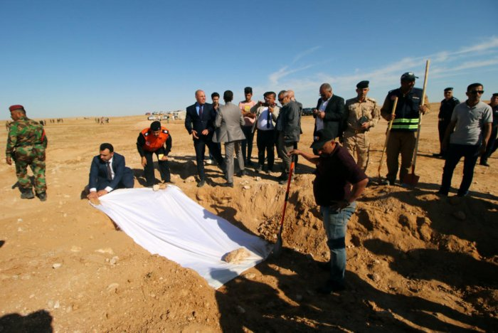 Iraqi members of the Civil Defense and officials cover the bones from an unearthed mass grave of Kurds in the west of the city of Samawa, Iraq. (Reuters Photo)
