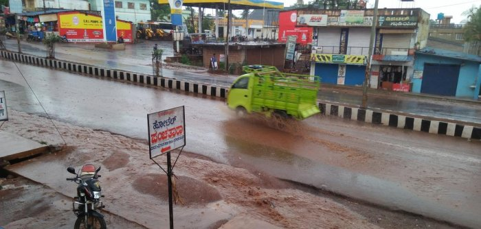 Water from drainage overflows on a road in Soraba, Shivamogga district following rain on Sunday. DH Photo
