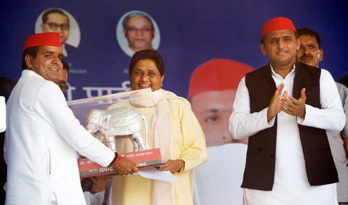 Bahujan Samaj Party supremo Mayawati being presented a memento by Samajwadi Party candidate Dharmendra Yadav as SP President Akhilesh Yadav claps, during their joint election campaign rally in Badaun, Saturday, April 13, 2019. (PTI Photo)