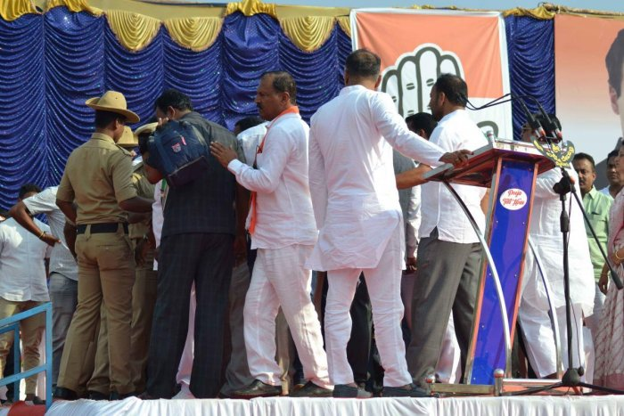 Members from the rebel faction of JD(S) ascend to the stage and shout slogans against JD(S) district president K M B Ganesh during an election campaign of coalition parties in Kushalnagar.
