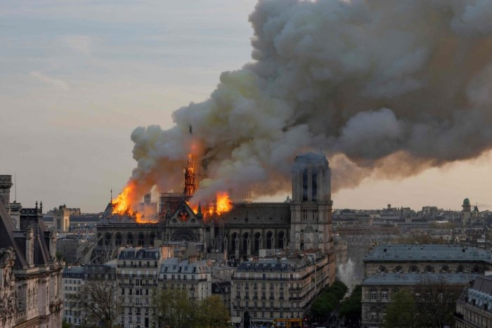 Smoke billows as flames burn through the roof of the Notre-Dame de Paris Cathedral on April 15, 2019, in the French capital Paris. - A huge fire swept through the roof of the famed Notre-Dame Cathedral in central Paris on April 15, 2019, sending flames and huge clouds of grey smoke billowing into the sky. The flames and smoke plumed from the spire and roof of the gothic cathedral, visited by millions of people a year. A spokesman for the cathedral told AFP that the wooden structure supporting the roof was b