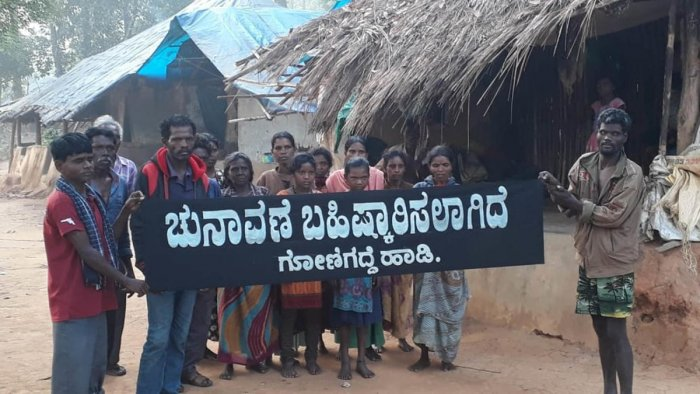 Residents of Gonigadde tribal hamlet display a banner, declaring the boycott of Lok Sabha elections.