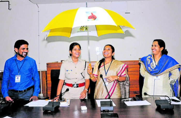Deputy Commissioner Hephsiba Rani Korlapati displays an umbrella, which has messages on the significance of voting, in Udupi on Tuesday. DH photo
