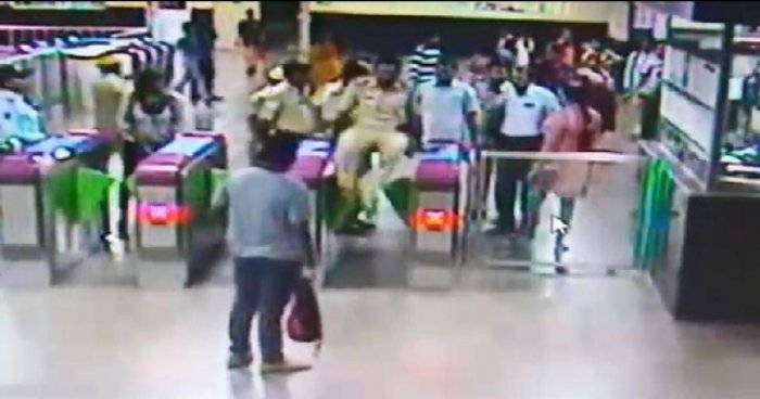 A sub-inspector jumps over the metro gates at Dasarahalli metro station.