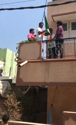 BJP corporator C R Ramamohan forcibly removes the flag from the first floor of a house at Viratnagar, Bommanahalli, on Monday.