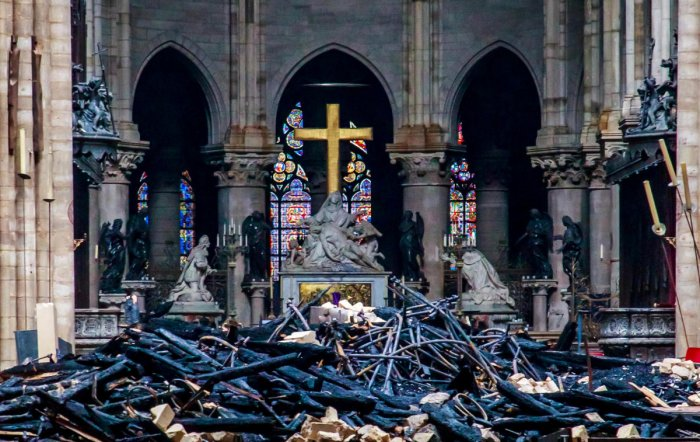 A view of the cross and sculpture of Pieta by Nicolas Coustou in the background of debris inside Notre-Dame de Paris, in the aftermath of a fire that devastated the cathedral, during the visit of French Interior Minister Christophe Castaner (not pictured)