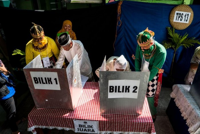 People cast their votes at a polling station during Indonesia's general election in Yogyakarta on April 17, 2019 (AFP)