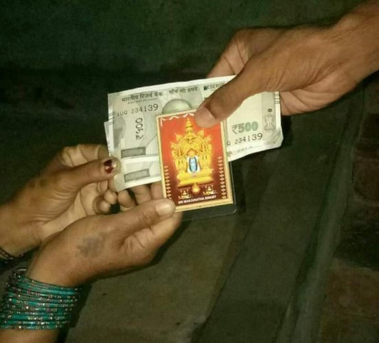 A photo of Dharmasthala Manjunatha Swamy being distributed along with money in Mandya.