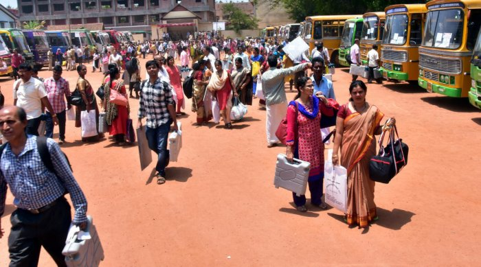 Polling officials leave mustering centre at St Cecily School in Udupi on Wednesday.