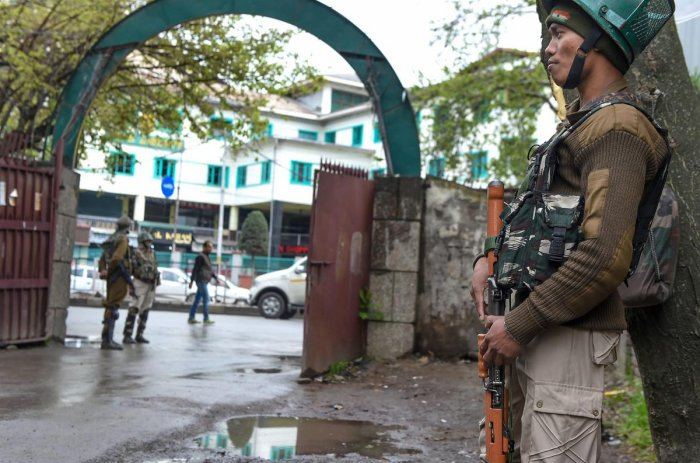 A security personnel stands guard outside an EVM distribution centre ahead of the second phase of Lok Sabha elections, in Srinagar on Wednesday. (PTI)