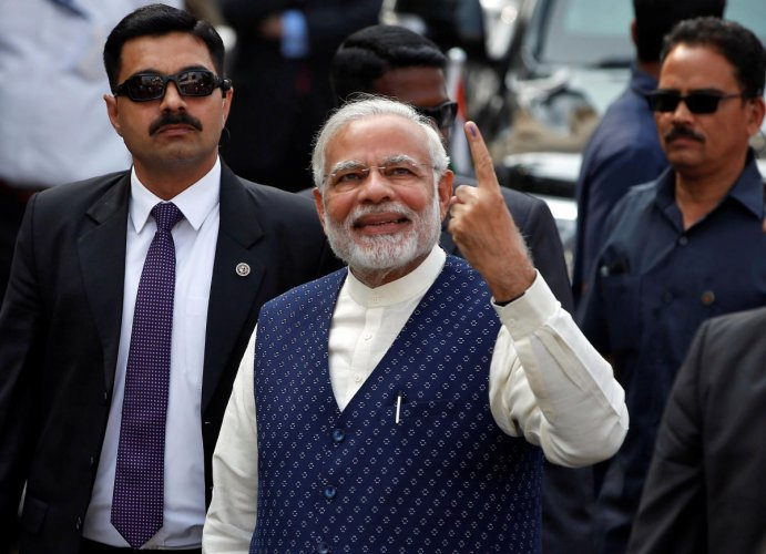 India's Prime Minister Narendra Modi shows his ink-marked finger after casting his vote outside a polling station during the last phase of Gujarat state assembly election in Ahmedabad, India, December 14, 2017. REUTERS/Amit Dave