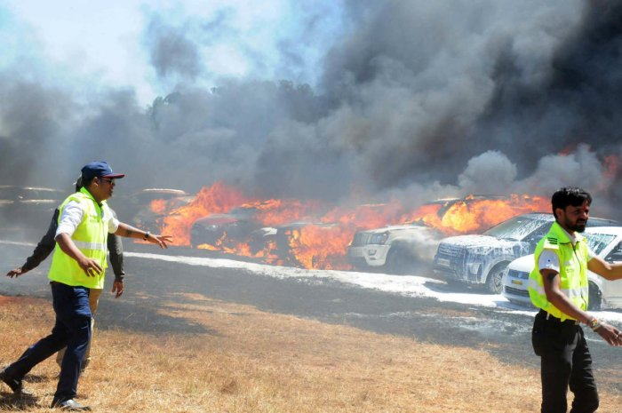Civil Defence workers in action as the flames engulf cars. DH Photo