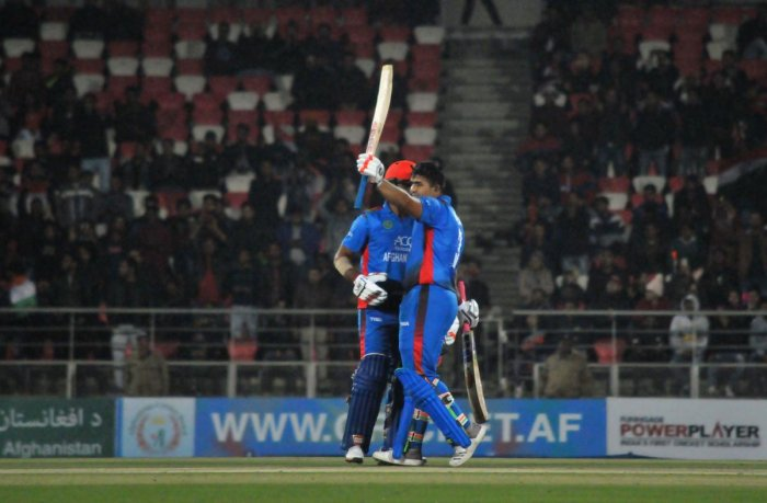 Afghanistan batsman Hazratullah Zazai (right) celebrates after reaching his century against Ireland in the second T20I in Dehradun on Saturday. AFP