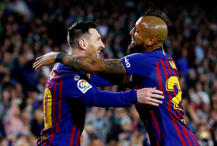 Barcelona's Lionel Messi celebrates with Arturo Vidal after scoring his first goal against Real Betis on Sunday. REUTERS