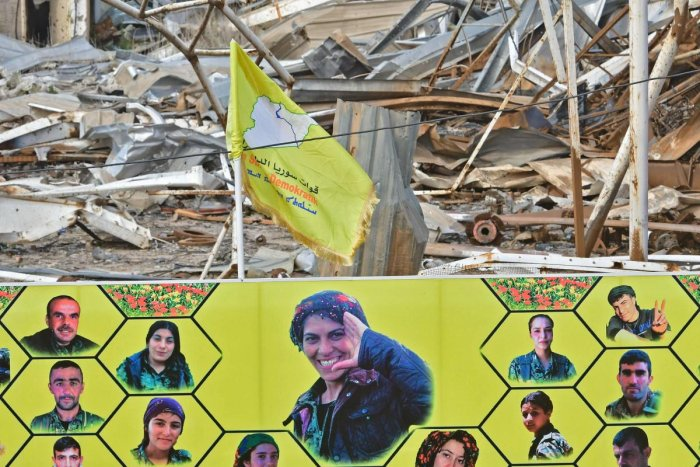 A woman stands by a large banner showing the faces of fighters of the US-backed Kurdish-led Syrian Democratic Forces (SDF), who were killed during battles with the Islamic State (IS) group, near the Omar oil field in the eastern Syrian Deir Ezzor province