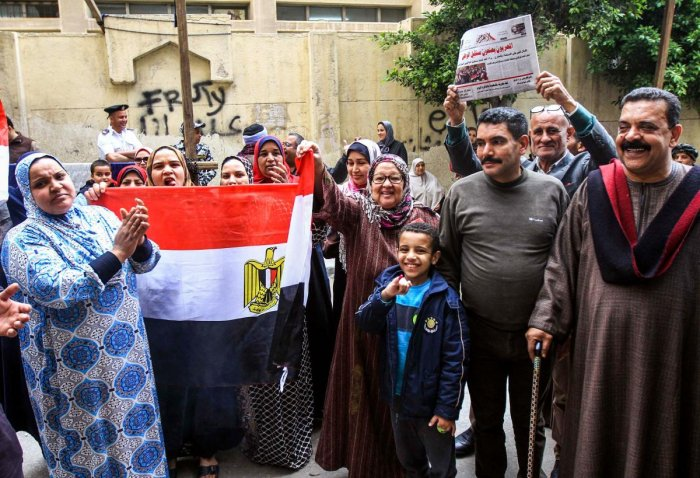 Egyptians pose for a picture with a national flag, a newspaper front page, and a poster of President Abdel Fattah al-Sisi. AFP