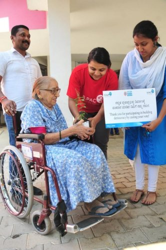 Archana M V from B.PAC gives away a tulsi sapling to a senior citizen who took the trouble to vote.