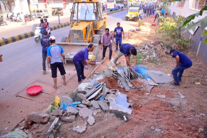 Volunteers clean the debris at Bendoorwell area in Mangaluru.
