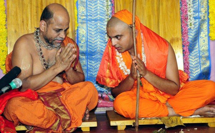 Puttige Mutt seer Sugunendratheertha Swami with his successor Sushreendratheertha Swami during the anointment ceremony at Hiriyadka in Udupi district on Monday. dh photo