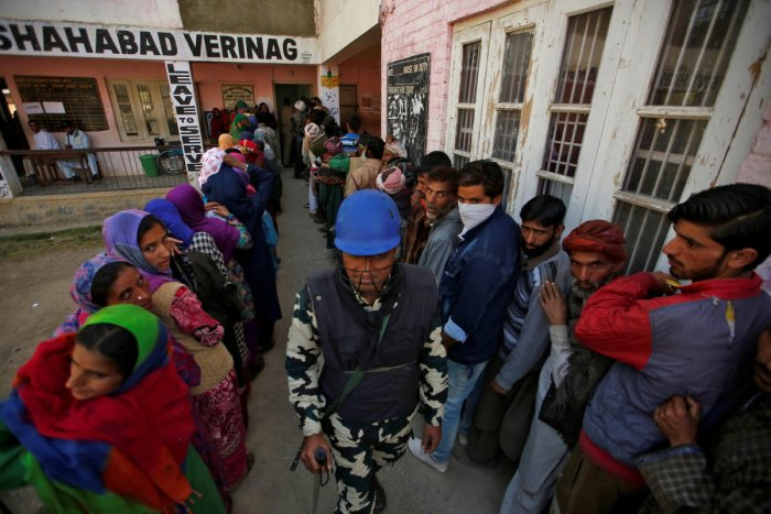 An Indian policeman stands guard as people wait in queues to cast their votes outside a polling station during the third phase of general election in Verinag in south Kashmir's Anantnag district April 23, 2019. (REUTERS)