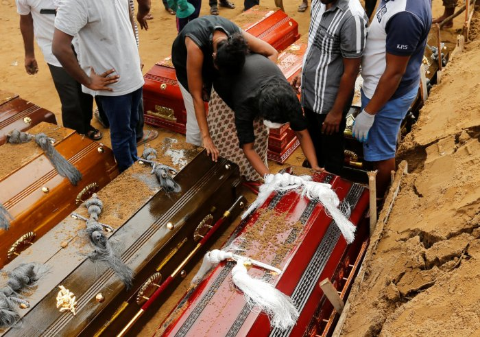 Coffins are laid in the ground during a mass burial for victims at a cemetery near St Sebastian's Church in Negombo, three days after a string of suicide bomb attacks on churches and luxury hotels across the island on Easter Sunday, in Sri Lanka April 24,