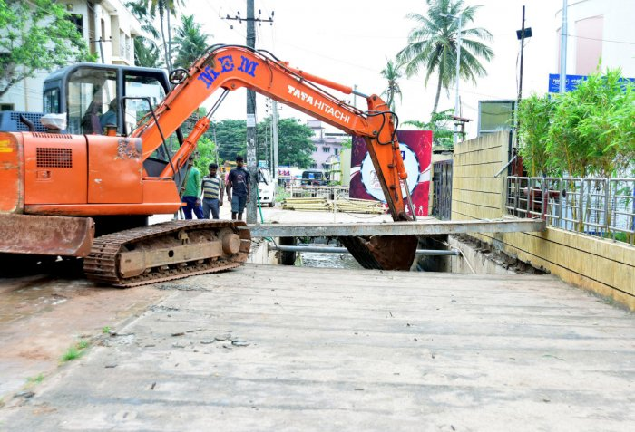 Men in action at the encroachment clearance drive undertaken at Kottara Chowki in Mangaluru on Monday. DH PHOTO