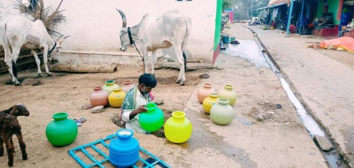 A resident of M Kodihalli in Kadur taluk collects water.