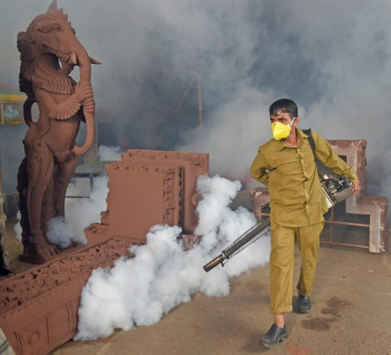 A BMC worker carries out fumigation works at a Ganpati pandal as part of preventive measures against Malaria. PTI