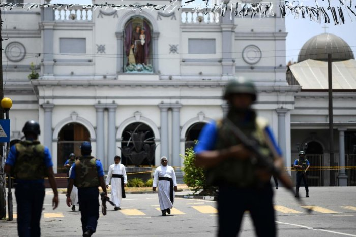 Priests walk on a blocked street as soldiers stand guard outside St. Anthony's Shrine in Colombo on April 25, 2019, following a series of bomb blasts targeting churches and luxury hotels on the Easter Sunday in Sri Lanka. - All of Sri Lanka's Catholic chu