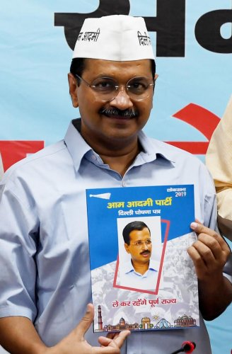 Chief Minister of Delhi Arvind Kejriwal looks on as he poses with a copy of the Aam Aadmi Party election manifesto at the party headquarters in New Delhi on April 25, 2019. (AFP)