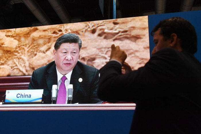 A journalist takes photos as a screen behind him shows a live image of Chinese President Xi Jinping speaking at the leaders summit of the Belt and Road Forum, in the media center of the Forum in Beijing on April 27, 2019. (AFP)