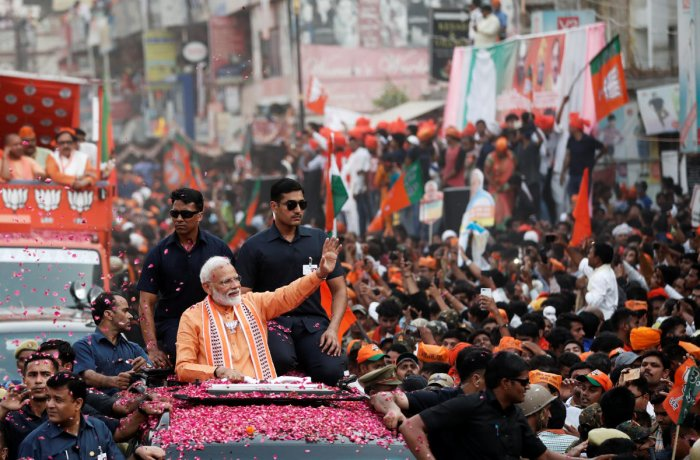 Prime Minister Narendra Modi waves towards his supporters during a roadshow in Varanasi. (Reuters Photo)
