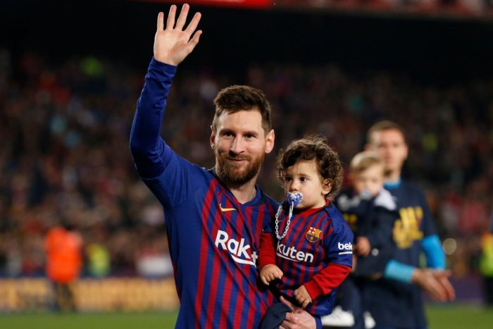 Barcelona's Argentinian forward Lionel Messi holds his son Ciro as he celebrates after Barcelona won their 26th league title at the end of the Spanish League football match between Barcelona and Levante at the Camp Nou stadium in Barcelona. AFP