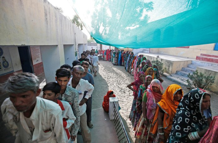 People wait in queues to cast their vote at a polling station at Sirohi district in Rajasthan. (Reuters Photo)