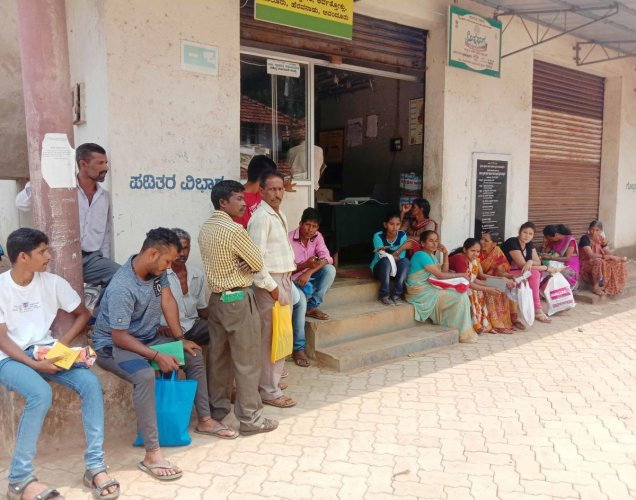 People wait outside the fair price shop near the Gram Panchayat office in Bettageri.