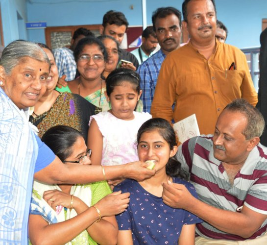 Family members and friends feed sweet to Srujana D, a student of St Philomena English High School, Attibele, who has scored 625/625 in SSLC examination, in Anekal on Tuesday.