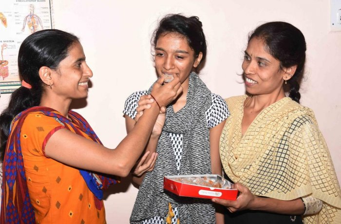 Megha Maradi of Presentation High School, Dharwad, who scored 92% in SSLC, is offered sweets by her mother Mallamma. dh photos