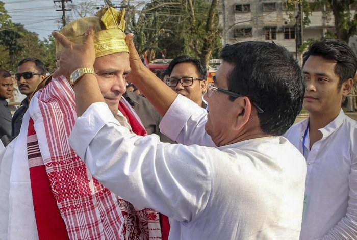 National Congress President Rahul Gandhi being welcomed on his arrival for an election campaign rally in Lakhimpur, Assam onWednesday. (PTI Photo)