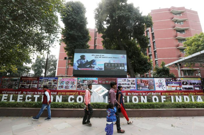 FILE PHOTO: People walk past the Election Commission of India office building in New Delhi, India March 11, 2019. REUTERS/Adnan Abidi/File Photo